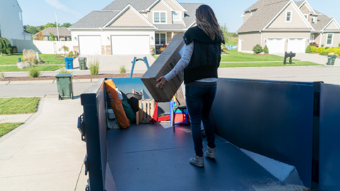 Woman Carrying Junk Into a Blue Roll Off Dumpster
