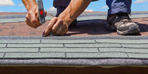 Roofer's Hands Nailing Down Shingles