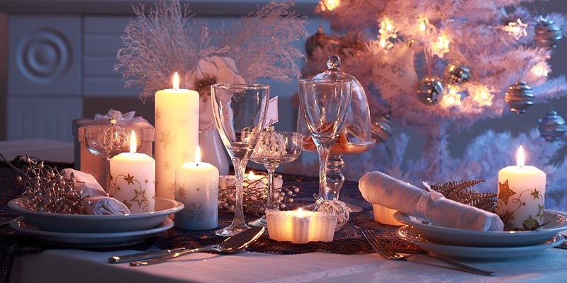 White Holiday Decorations and Dishes in a Candle-Lit Room
